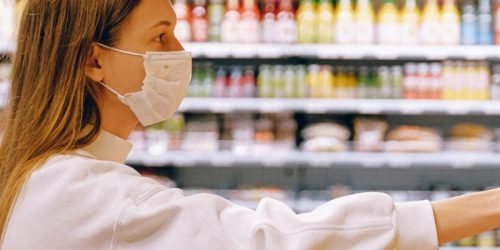 Woman shops in grocery store wearing facemask during COVID-19